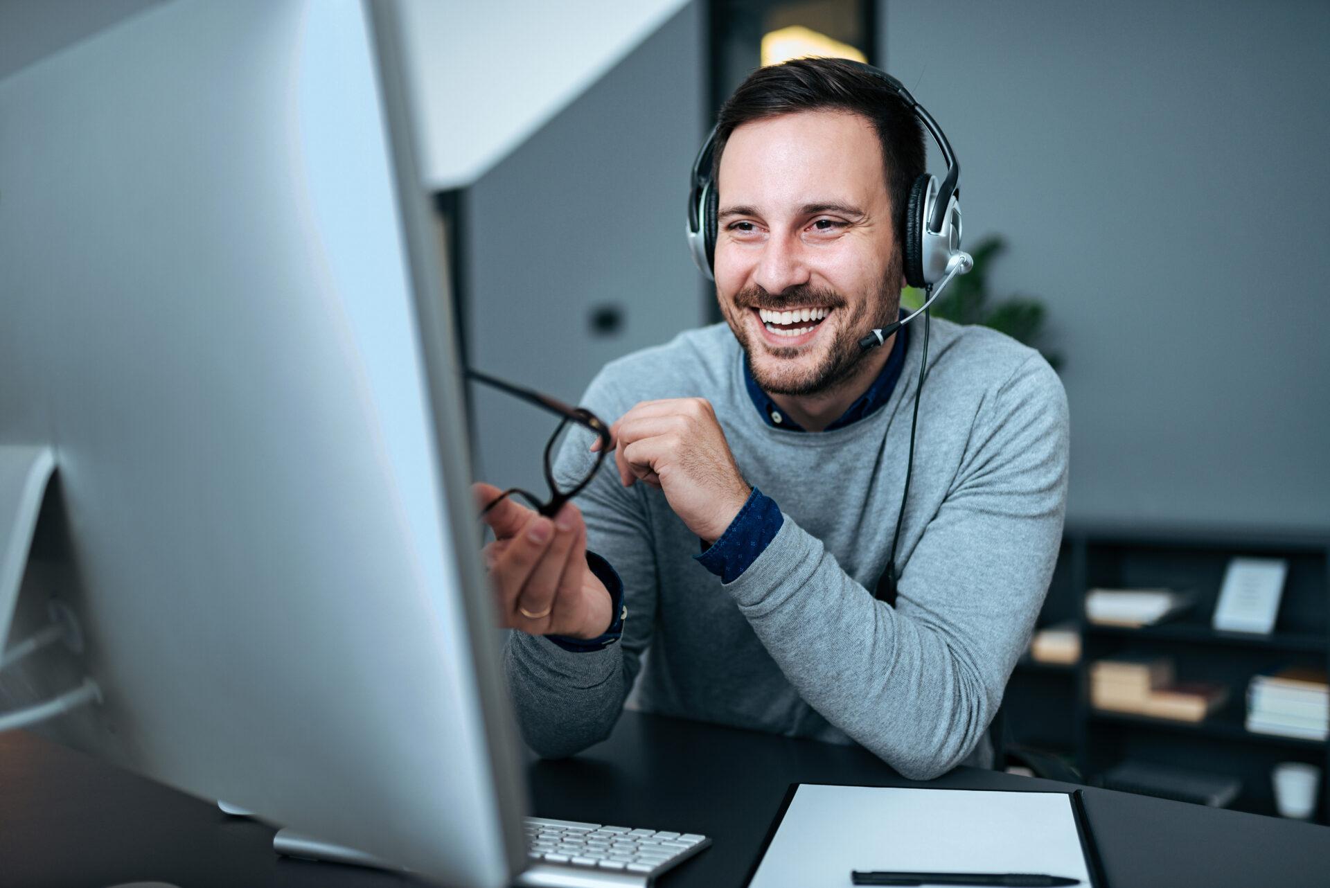 Mann mit Headset lacht und schaut in den Bildschirm