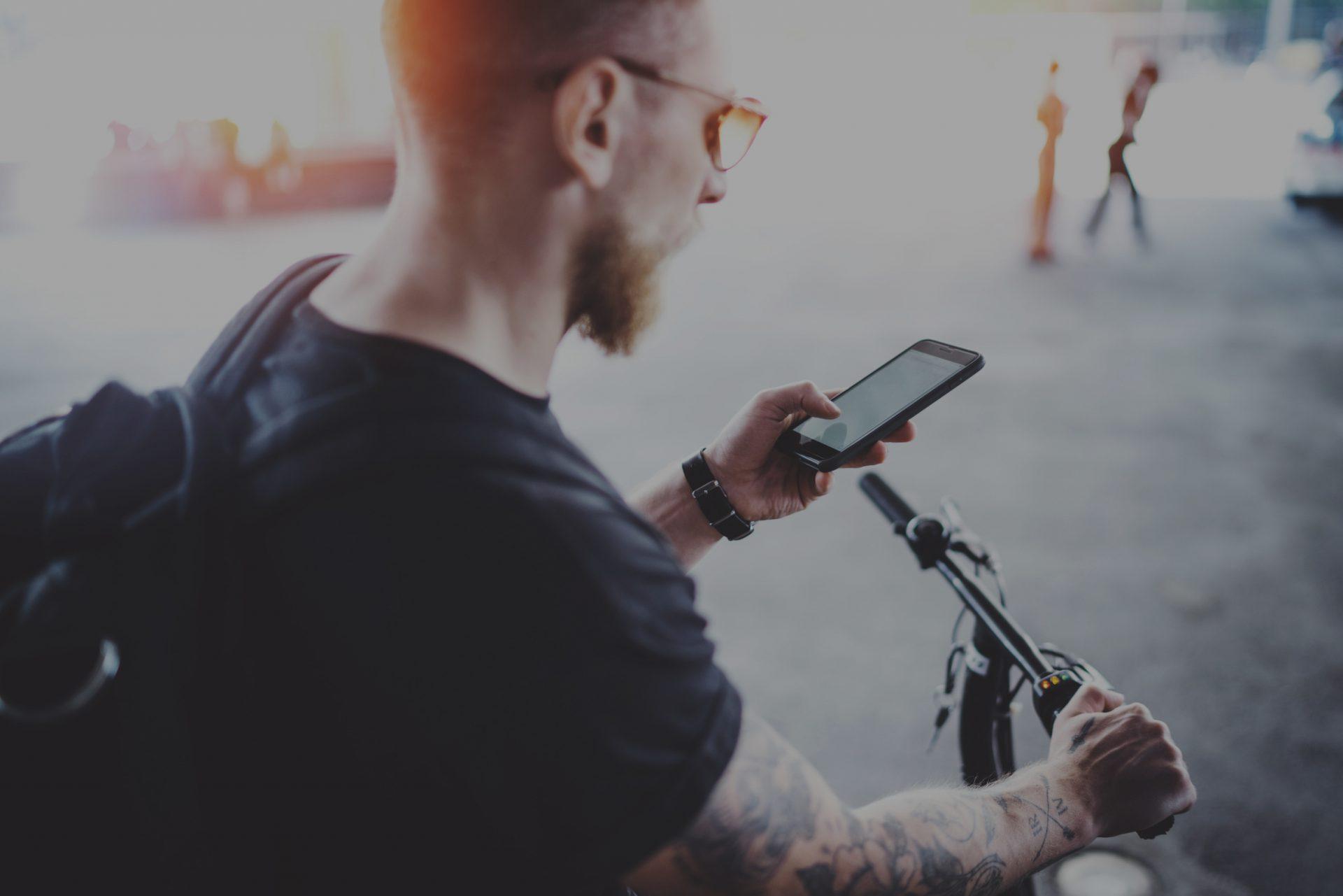 Mann unterwegs mit einem E-Scooter und Handy in der Hand