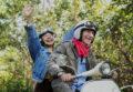 Älteres Ehepaar fährt jubelnd zusammen auf einem E-Roller durch die Natur