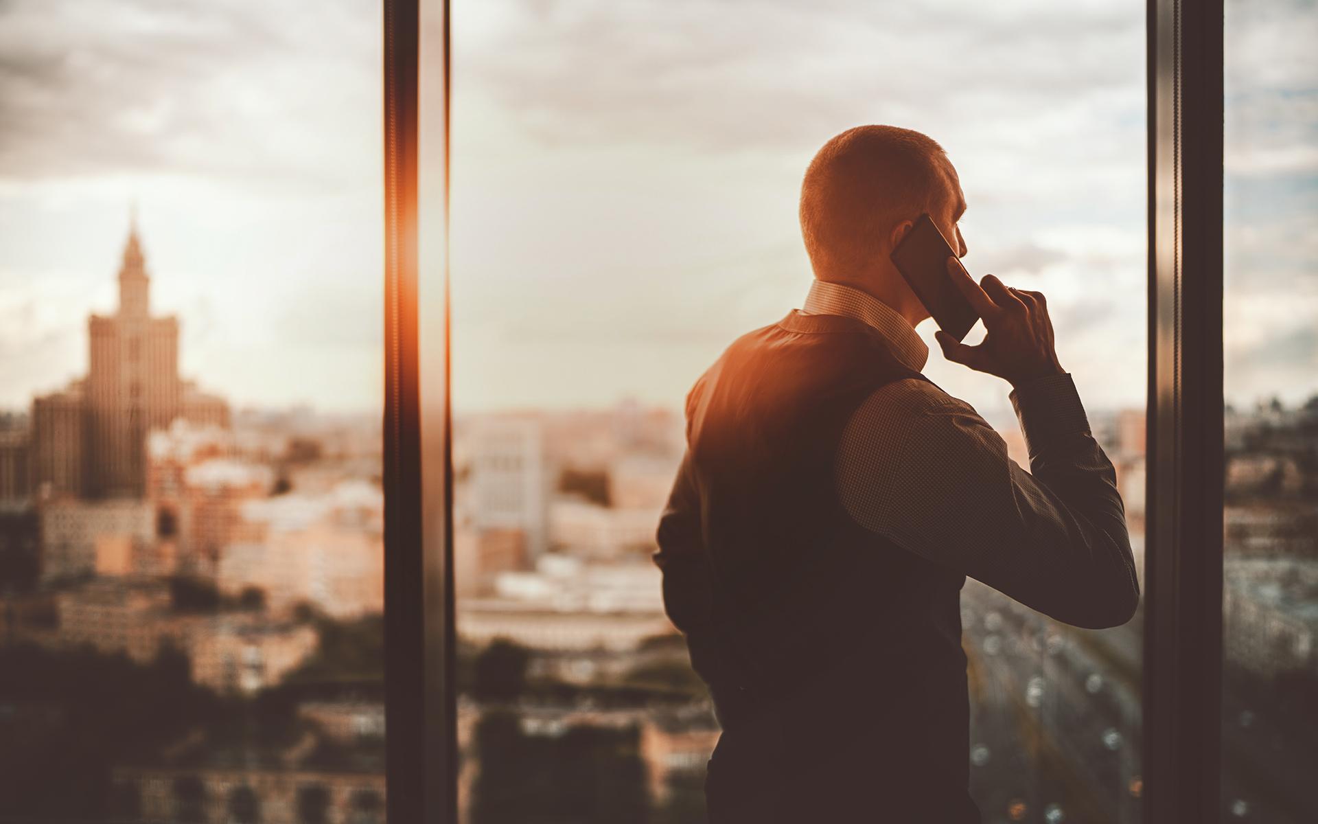 Mann telefoniert und schaut aus dem Fenster über eine Stadt