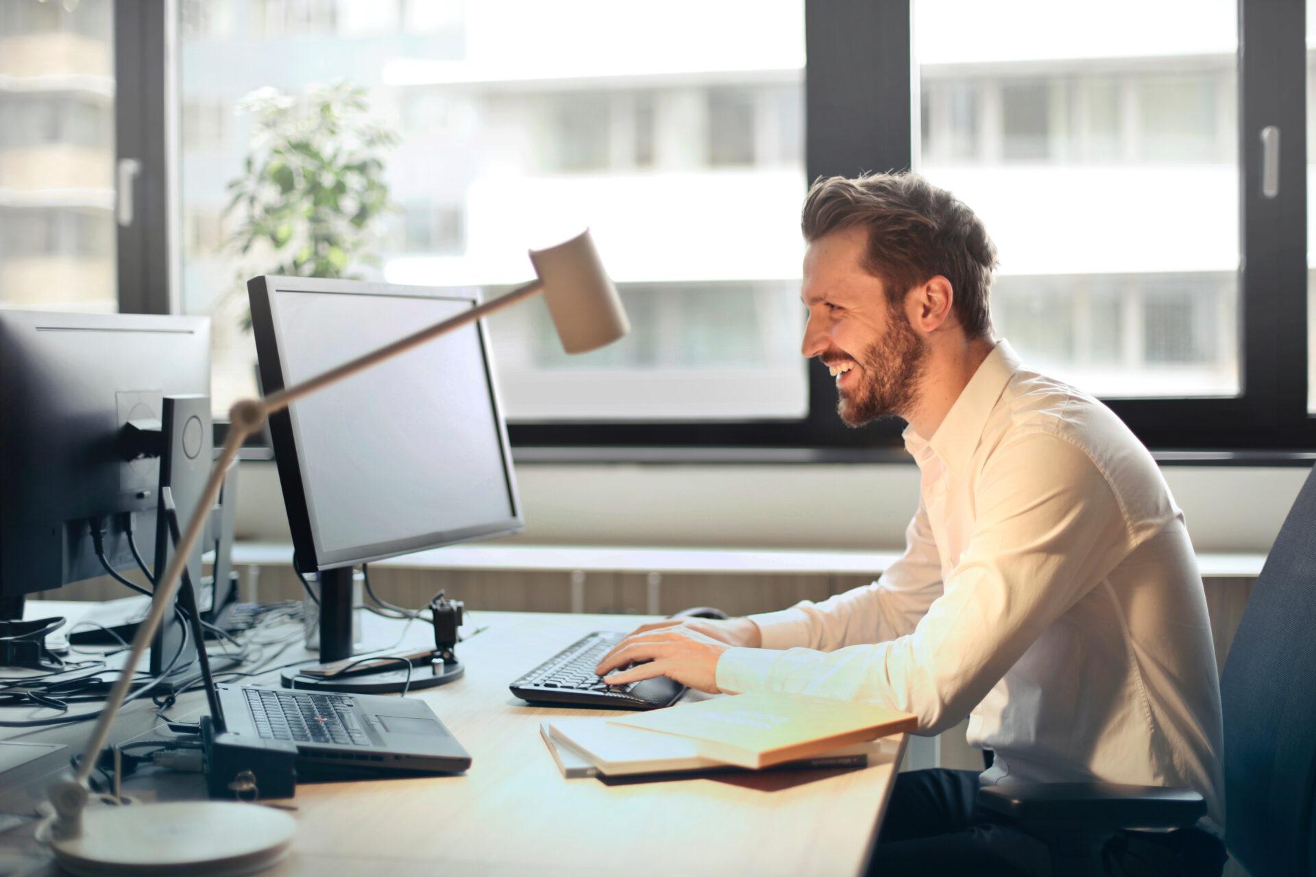 Mann lächelt in seinen Bildschirm am Schreibtisch