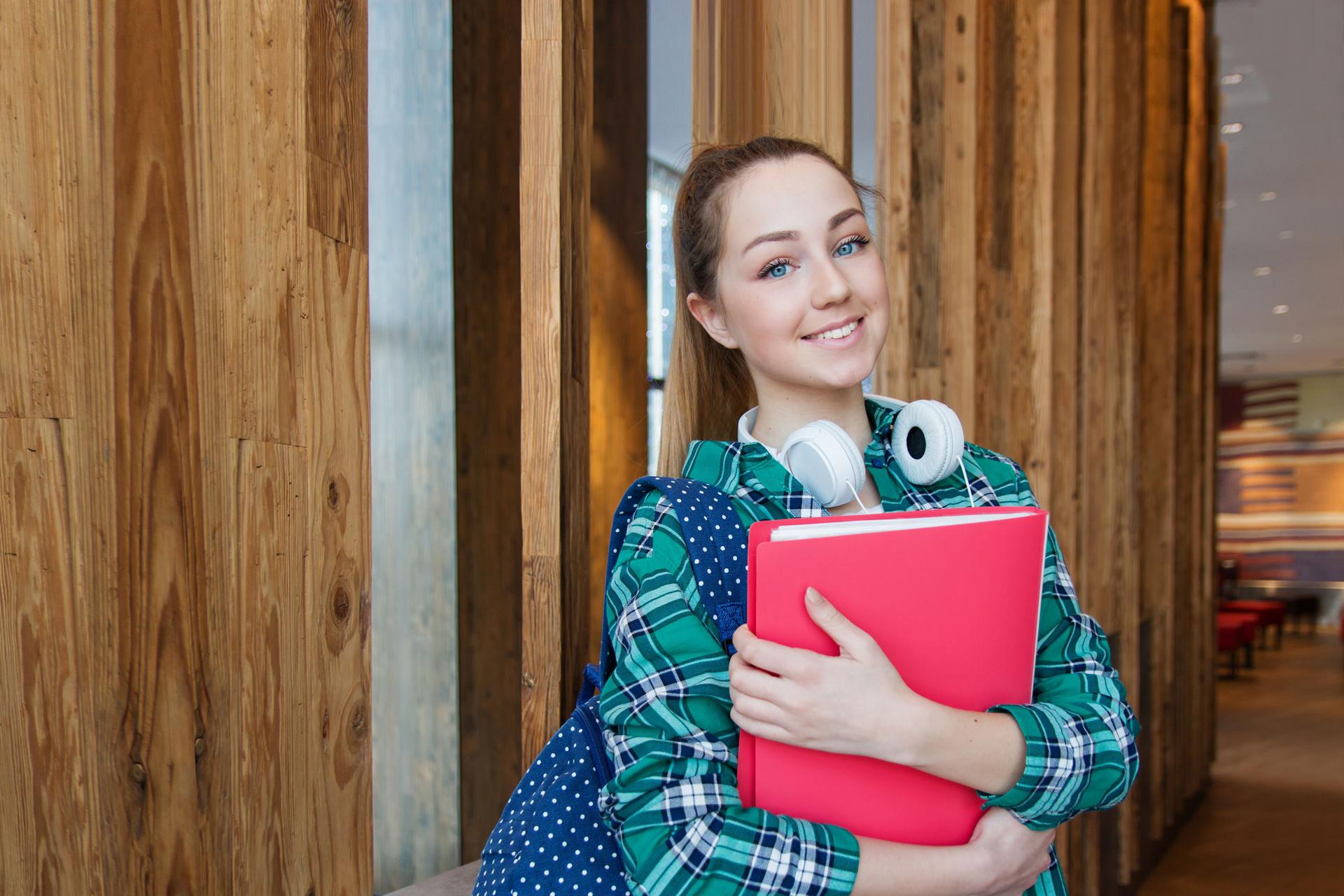 Studentin lächelt und hat eine Mappe in der Hand