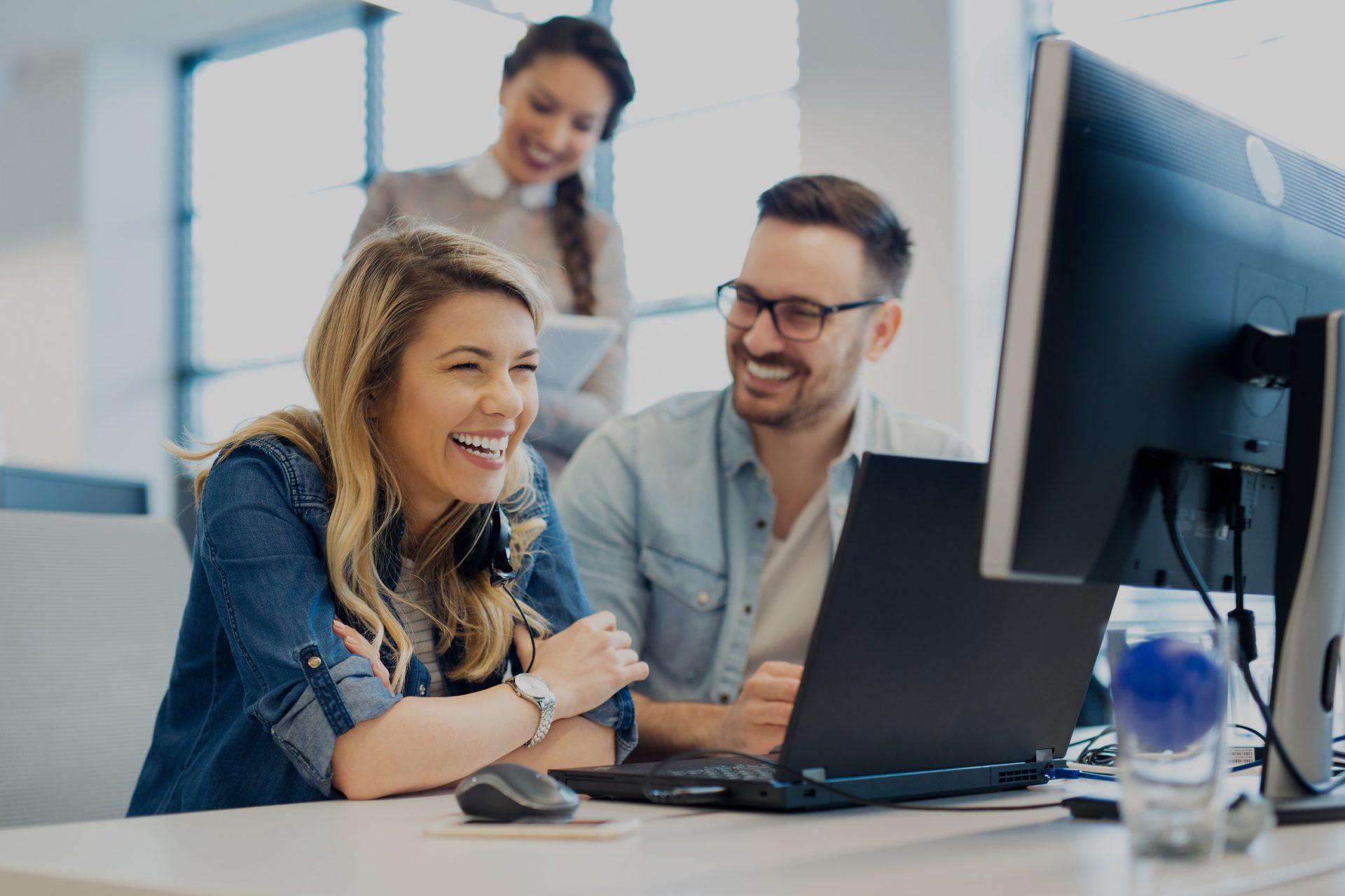 zwei Frauen und ein Mann lachen vor einem Bildschirm